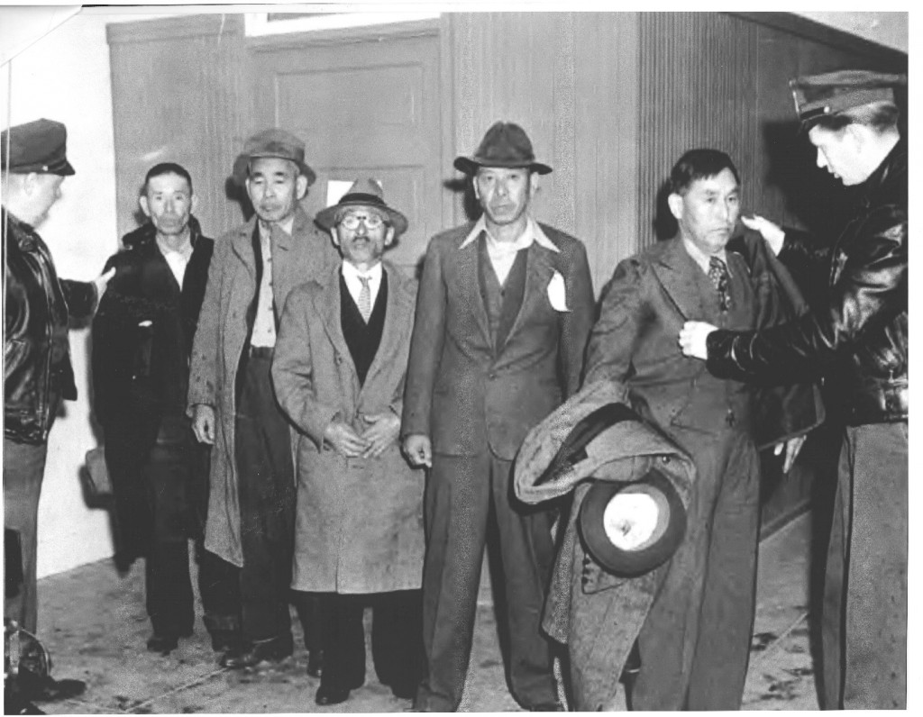 Nikuma Tanouye, next to the officer on the left, being arrested by the FBI.